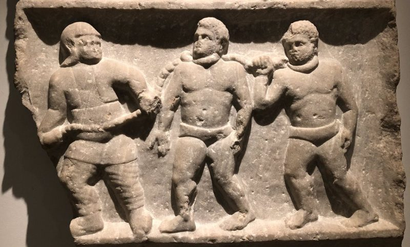 Roman legionary leads vanquished men bound in chains. The slave-owning mode of production will require continuous conquests to maintain a sufficient number of slaves for its productive needs.